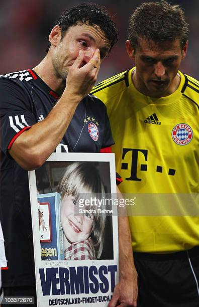 Mark van Bommel of Bayern cries while holding a sign for charity of missing children prior to the Franz Beckenbauer Farewell match between FC Bayern...