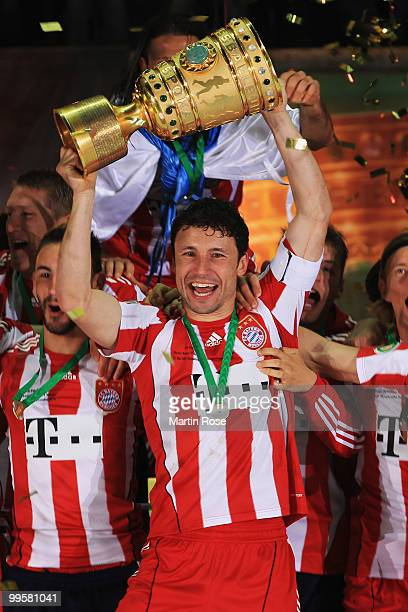 Mark van Bommel of Bayern Muenchen lifts the DFB Cup trophy following his team's victory at the end of the the DFB Cup final match between SV Werder...