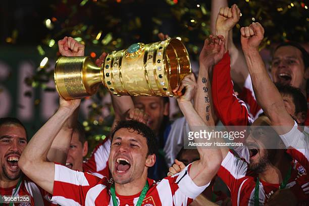 Mark van Bommel of Bayern Muenchen lifts the DFB Cup trophy following his team's victory at the end of the DFB Cup final match between SV Werder...