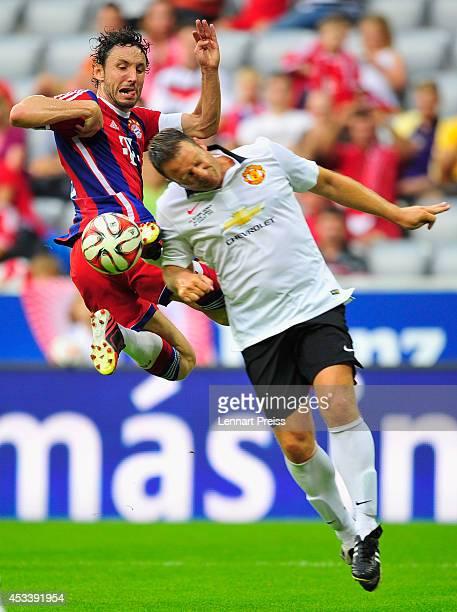 Mark van Bommel of FCB AllStars challenges Denis Irwin of ManUtd Legends during the friendly match between FC Bayern Muenchen AllStars and Manchester...