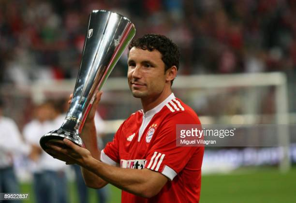Mark van Bommel of Muenchen holds the trophy after winning the Audi Cup tournament final match between FC Bayern Muenchen v Manchester United at...
