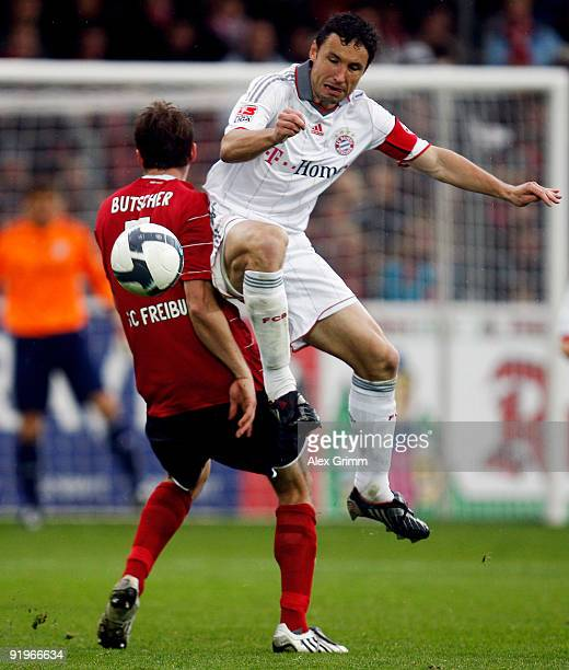 Mark van Bommel of Muenchen is challenged by Heiko Butscher of Freiburg during the Bundesliga match between SC Freiburg and Bayern Muenchen at the...