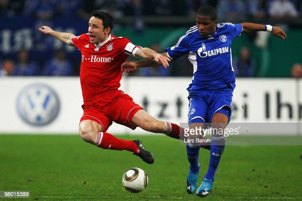 Mark van Bommel of Muenchen is challenged by Jefferson Farfan of Schalke during the DFB Cup semi final match between FC Schalke 04 and FC Bayern...