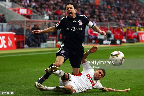 Mark van Bommel of Muenchen is challenged by Youssef Mohamad of Koeln during the Bundesliga match between 1 FC Koeln and FC Bayern Muenchen at...