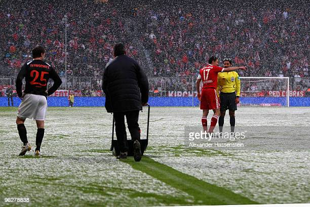 Mark van Bommel of Muenchen talks to Referee Babak Rafati whilts green keeper cleans the field during heavy snowfall at the Bundesliga match between...