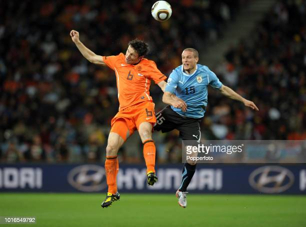 Mark Van Bommel of the Netherlands and Diego Perez of Uruguay in action during the 2010 FIFA World Cup Semi Final match between Uruguay and the...