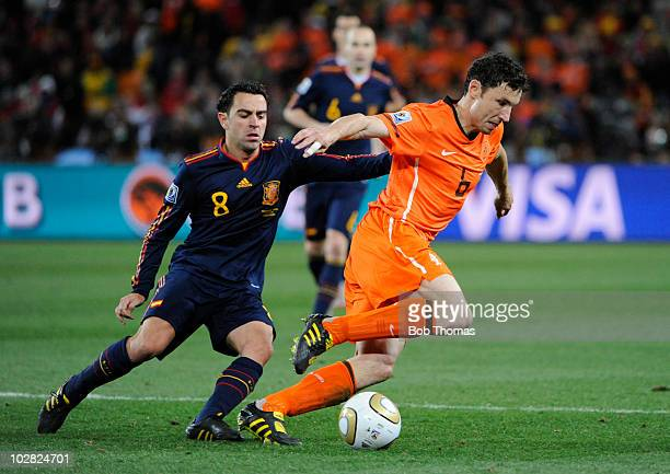 Mark Van Bommel of the Netherlands challenged by Xavi of Spain during the 2010 FIFA World Cup Final between the Netherlands and Spain on July 11 2010...