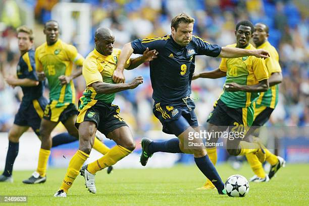 Mark Viduka of Australia is challenged by Franck Sinclair of Jamaica during the International friendly match between Australia and Jamaica at The...