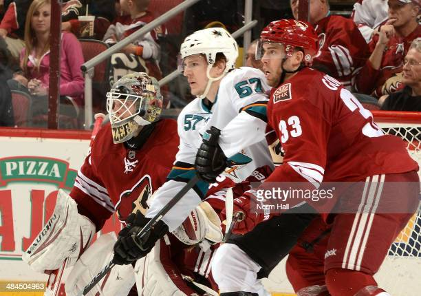 Mark Visentin of the Phoenix Coyotes gets ready to make a save as teammate Brandon Gormley battles for position with Tommy Wingels of the San Jose...