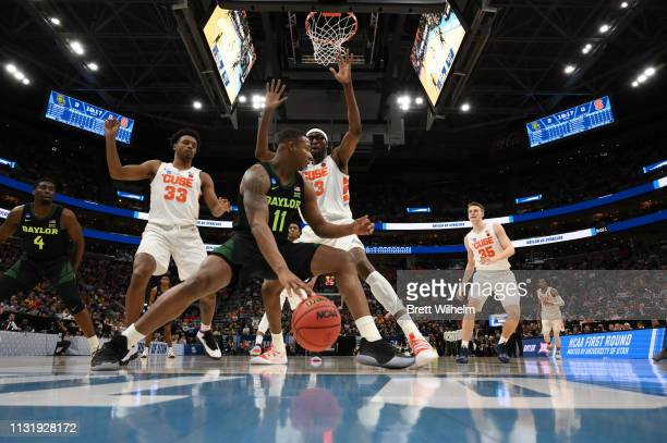 Mark Vital of the Baylor Bears dribbles under the basket while being defended by Paschal Chukwu of the Syracuse Orangeduring the game between the...