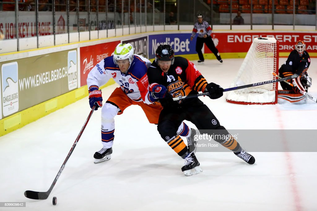 Mark Voakes (R) of Wolfsburg and Joona Luoto of Tampere battle for the puck during the Champions Hockey League match between Grizzlys Wolfsburg and Tappara Tampere at Eis Arena Wolfsburg on August 27, 2017 in Wolfsburg, Germany.