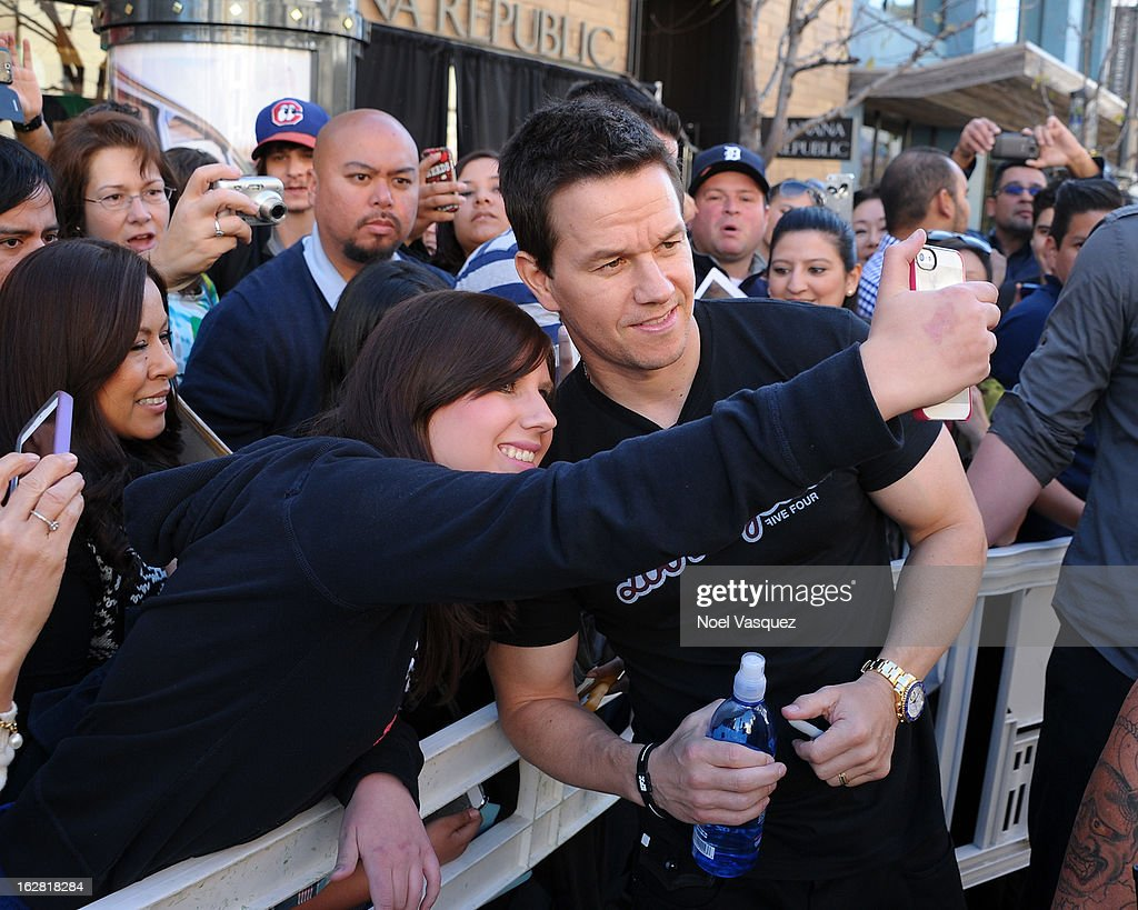 Mark Wahlberg poses with fans at Extra at The Grove on February 27, 2013 in Los Angeles, California.
