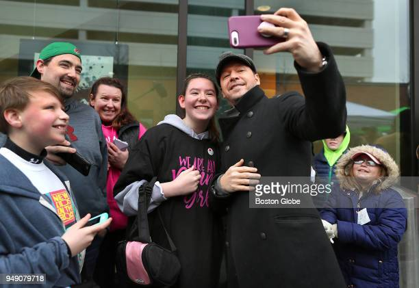 Mark Wahlberg takes a selfie with Brynn Schroeder from Bangor ME as she waits in line to try a hamburger at the new Wahlburgers food truck parked at...