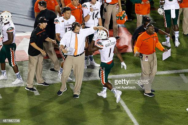 Mark Walton is congratulated by Head coach Al Golden of the Miami Hurricanes after scoring a first quarter touchdown against the Florida Atlantic...