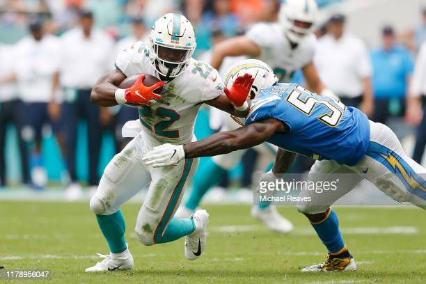 Mark Walton of the Miami Dolphins is tackled by Denzel Perryman of the Los Angeles Chargers during the second quarter at Hard Rock Stadium on...