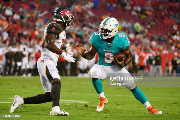 Mark Walton of the Miami Dolphins looks to get around Jordan Whitehead of the Tampa Bay Buccaneers in the second quarter of a preseason football game...