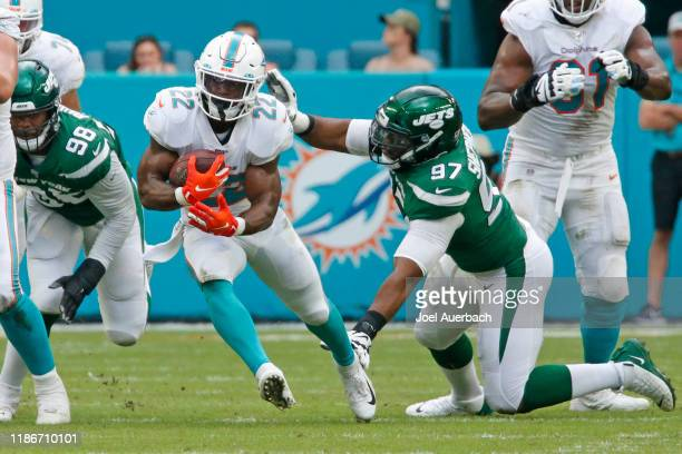 Mark Walton of the Miami Dolphins runs past the attempted tackle of Nathan Shepherd of the New York Jets during an NFL game on November 3 2019 at...