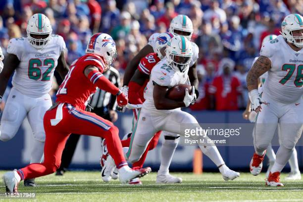Mark Walton of the Miami Dolphins runs the ball as Jordan Poyer of the Buffalo Bills attempts to tackle him during the fourth quarter of an NFL game...