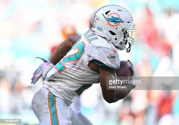 Mark Walton of the Miami Dolphins runs with the ball against the Washington Redskins in the fourth quarter at Hard Rock Stadium on October 13 2019 in...