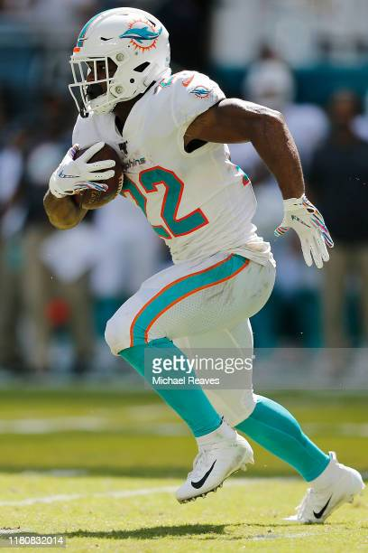 Mark Walton of the Miami Dolphins runs with the ball against the Washington Redskins during the second quarter at Hard Rock Stadium on October 13...