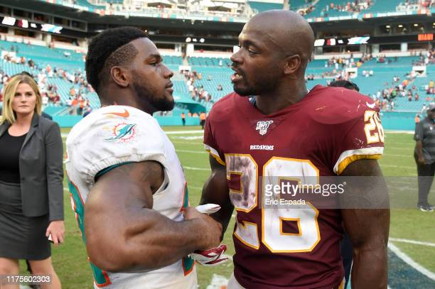 Mark Walton of the Miami Dolphins shakes hands with Adrian Peterson of the Washington Redskins after the game at Hard Rock Stadium on October 13 2019...