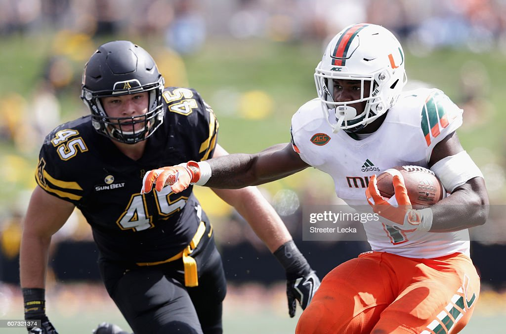 Mark Walton #1 of the Miami Hurricanes runs past Eric Boggs #45 of the Appalachian State Mountaineers during their game at Kidd Brewer Stadium on September 17, 2016 in Boone, North Carolina.