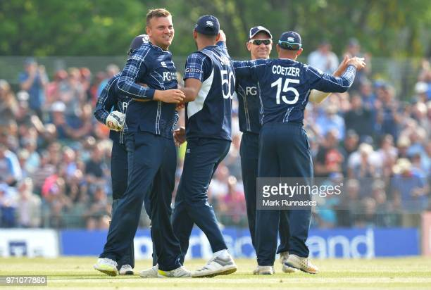 Mark Watt of Scotland celebrates with his team mates after taking the wicket of Sam Billings of England during the One Day International match...