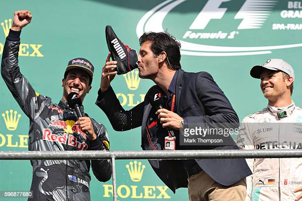Mark Webber drinks champagne from the boot of Daniel Ricciardo of Australia and Red Bull Racing on the podium during the Formula One Grand Prix of...