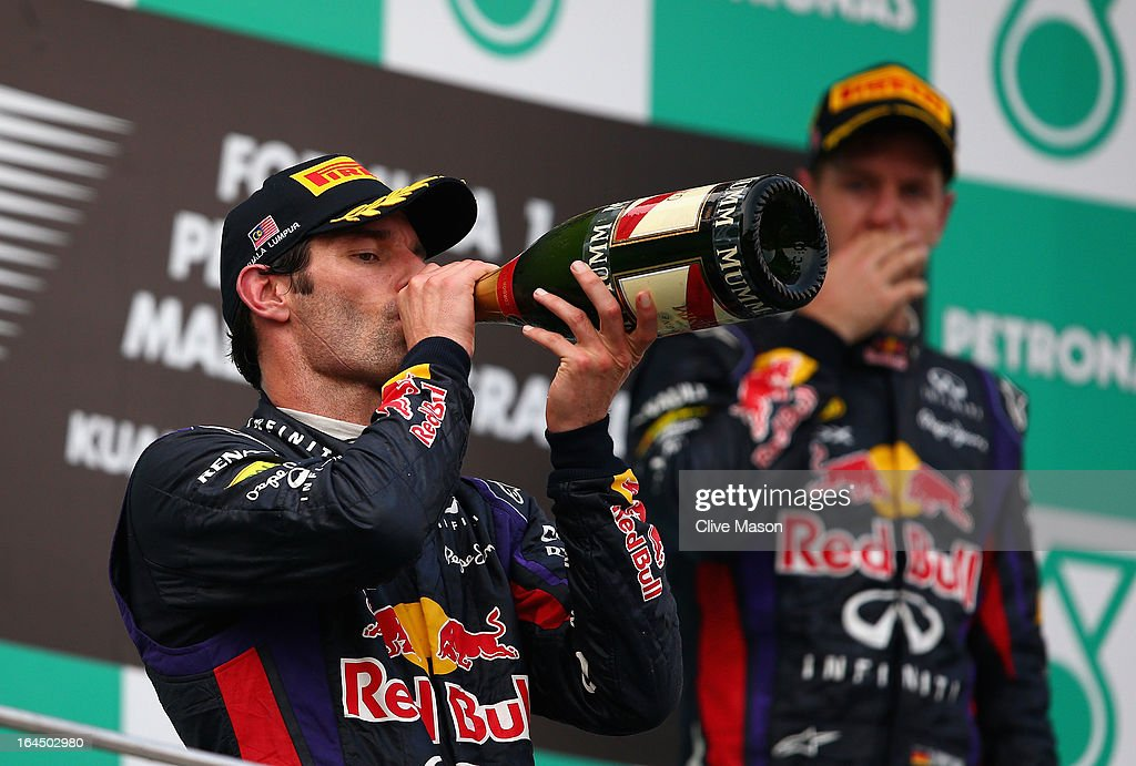 Mark Webber (L) of Australia and Infiniti Red Bull Racing celebrates finishing second as race winner Sebastian Vettel of Germany and Infiniti Red Bull Racing reacts on the podium following the Malaysian Formula One Grand Prix at the Sepang Circuit on March 24, 2013 in Kuala Lumpur, Malaysia.