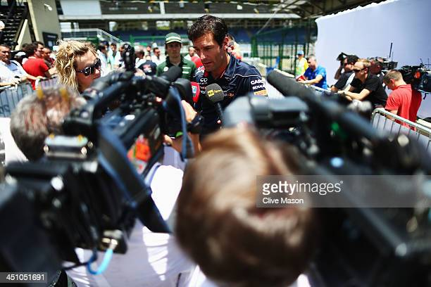 Mark Webber of Australia and Infiniti Red Bull Racing is interviewed by the media after attending his final drivers press conference during previews...