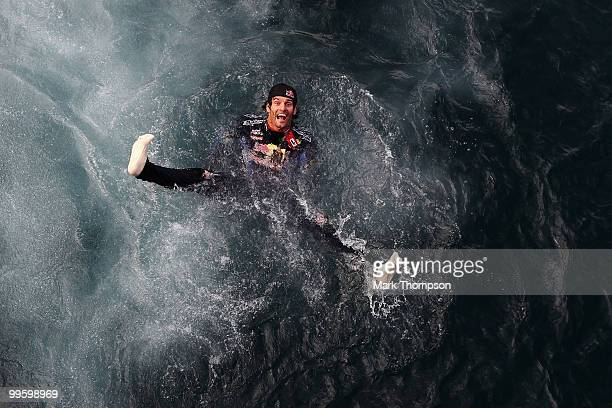 Mark Webber of Australia and Red Bull Racing celebrates by diving into the harbour after winning the Monaco Formula One Grand Prix at the Monte Carlo...