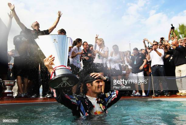 Mark Webber of Australia and Red Bull Racing celebrates by diving into the Red Bull Energy Station swimming pool after winning the Monaco Formula One...