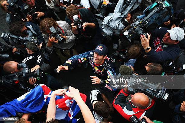 Mark Webber of Australia and Red Bull Racing celebrates with team mates in the paddock after winning the German Formula One Grand Prix at Nurburgring...