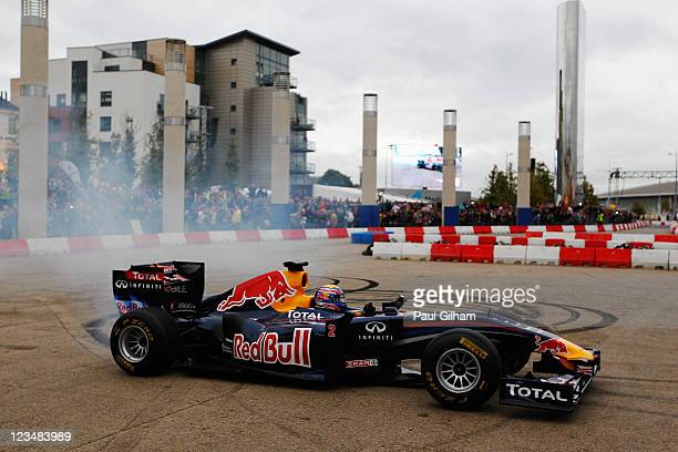 Mark Webber of Australia and Red Bull Racing does donuts for the fans after driving his F1 car through the city streets during the Red Bull Speed Jam...