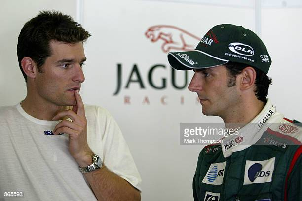 Mark Webber of Australia talks to Pedro De La Rosa of Spain prior to testing the Jaguar R3 Formula 1 car at the Cricuit de Catalunya near Barcelona,...