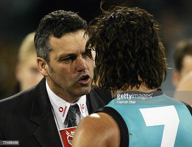 Mark Williams coach of Port Adelaide speaks with Peter Burgoyne for Port Adelaide during the round twenty one AFL match between the Collingwood...