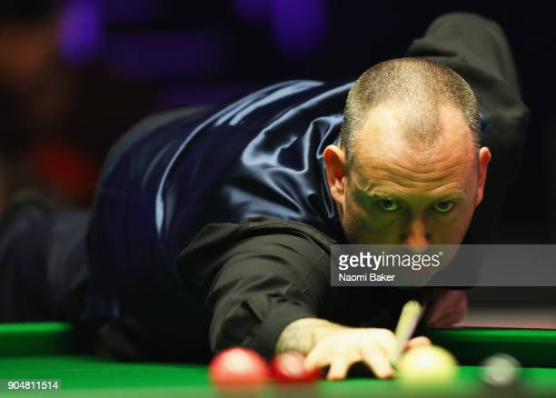 Mark Williams of Wales plays a shot during his match against Mark Selby of England on day one of The Dafabet Masters at Alexandra Palace on January...