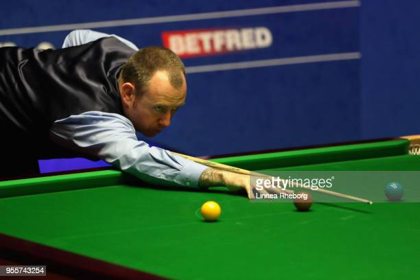 Mark Williams of Wales plays a shot during the fourth session of the final against John Higgins of Scotland during day seventeen of World Snooker...
