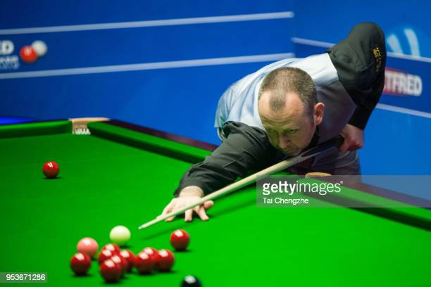 Mark Williams of Wales plays a shot in the quarterfinal match against Ali Carter of England during day eleven of the World Snooker Championship at...