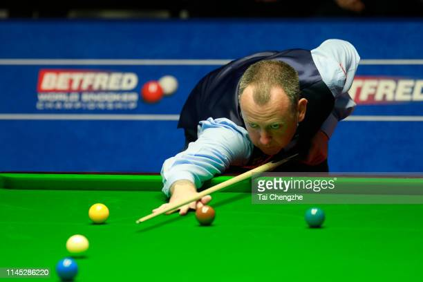 Mark Williams of Wales plays a shot in the second round match against David Gilbert of England during day seven of the 2019 Betfred World Snooker...