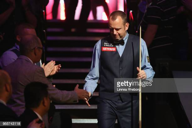 Mark Williams of Wales shakes hands with fans while making his entrance during the fourth session of the final against John Higgins of Scotland...