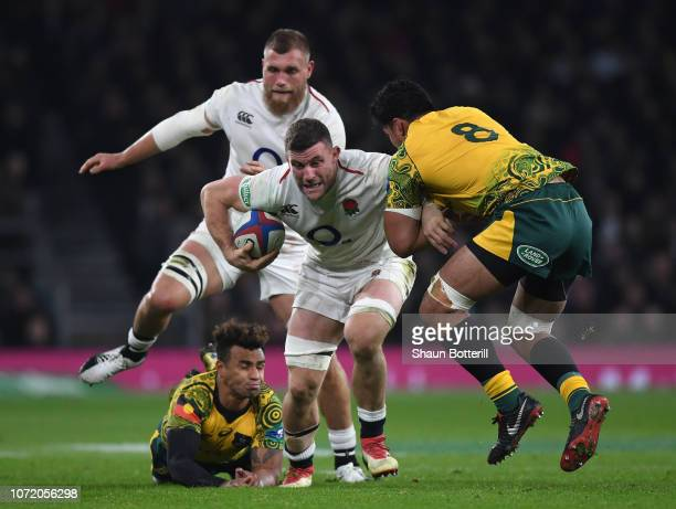 Mark Wilson of England breaks through the tackle of Pete Samu and Will Genia of Australia during the Quilter International match between England and...
