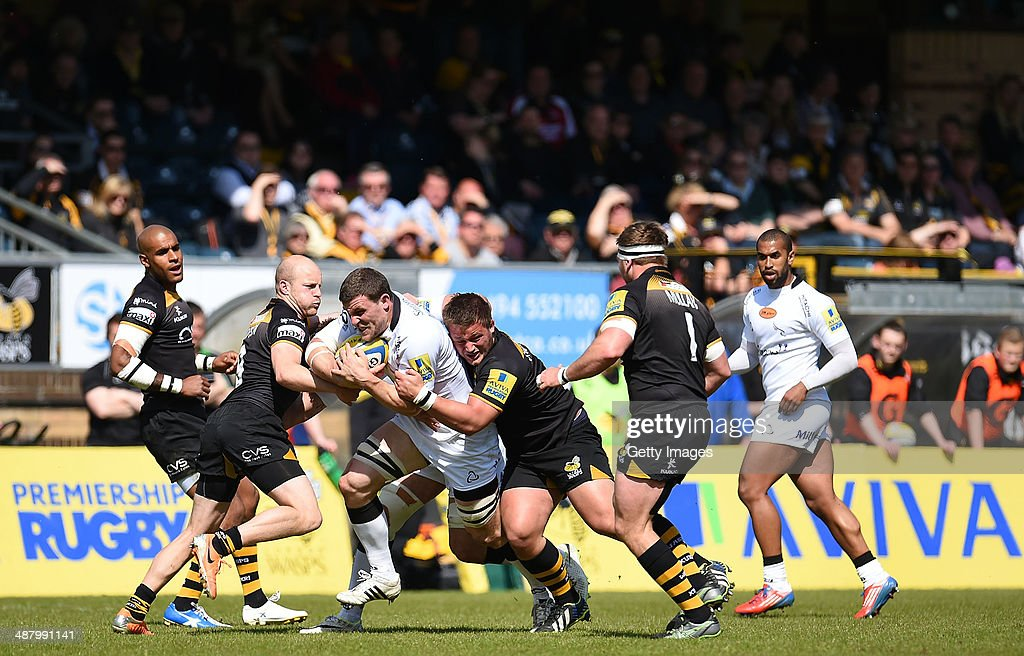 Mark Wilson of Newcastle Falcons is tackled by Joe Simpson (L) and Phil Swainston (R) of London Wasps during the Aviva Premiership match between London Wasps and Newcastle Falcons at Adams Park on May 03, 2014 in High Wycombe, England.