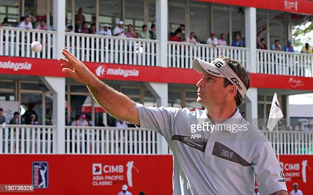 Mark Wilson of the US throws a ball to spectators after the last shot at hole eighteen during the third round of the CIMB Asia Pacific Classic golf...