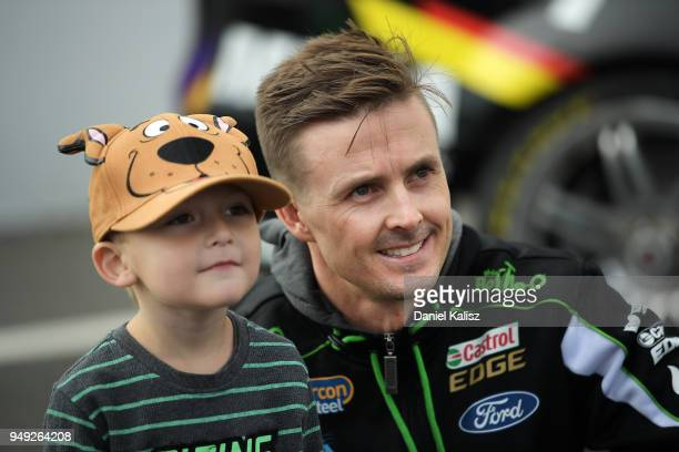 Mark Winterbottom driver of the The BottleO Racing Team Ford Falcon FGX poses for a photo with a fan during the Supercars Phillip Island 500 at...