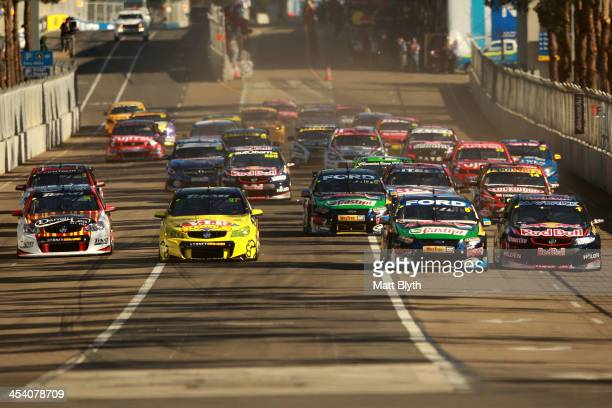 Mark Winterbottom drives the Pepsi Max Crew FPR Ford alongside Jamie Whincup driver of the Red Bull Racing Australia Holden at the start of the...