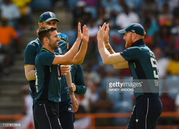 Mark Wood and Ben Stokes of England celebrate the dismissal of Shai Hope of West Indies during the 4th ODI between West Indies and England at Grenada...
