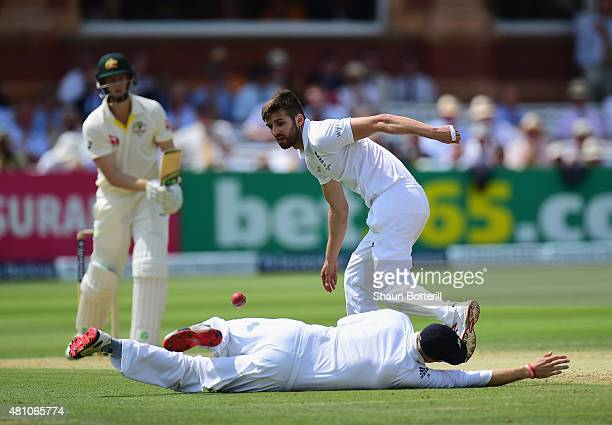 Mark Wood and Joe Root of England field the ball during day two of the 2nd Investec Ashes Test match between England and Australia at Lord's Cricket...