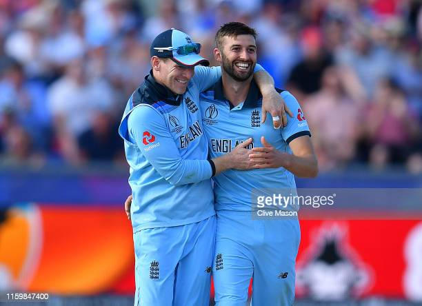 Mark Wood of England and captain Eoin Morgan of England celebrate the wicket of Mitchell Santner of New Zealand during the Group Stage match of the...