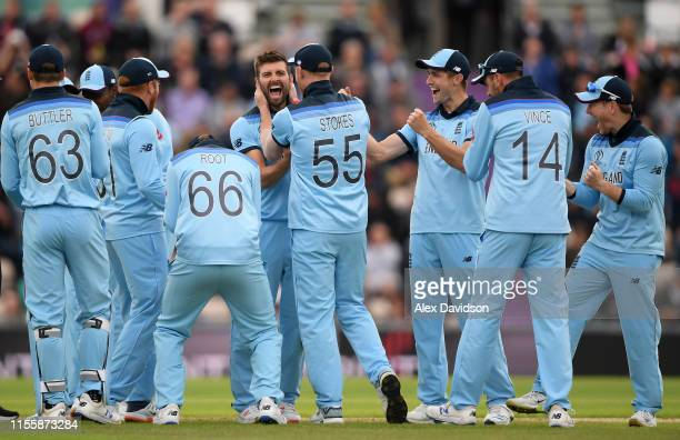 Mark Wood of England celebrates the successful review and wicket of Shai Hope of West Indies with his teammates during the Group Stage match of the...